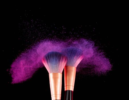Cosmetics brush and explosion makeup colorful dust powder background