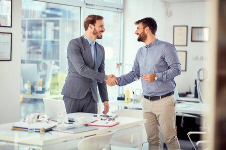 Junger Geschäftsmann hat erfolgreich ein Geschäftstreffen mit lächelnden Kunden abgeschlossen Standard-Bild