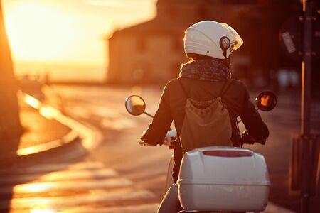 Mujer en scooter. Niña montando moto en la carretera.