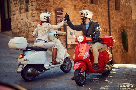 Giovani coppie italiane su scooter Vespa. Coppia di motociclisti.
