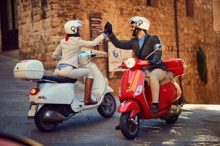 Joven pareja italiana en Vespa Scooter. Pareja de ciclistas.