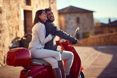 Gente de negocios sonriente en scooter. scooter en la ciudad. Joven pareja feliz montando scooter.