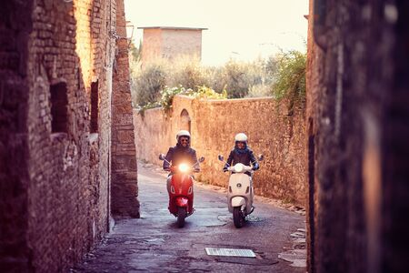 Smiling couple on motor scooter. Bikers on the road trip. Stockfoto