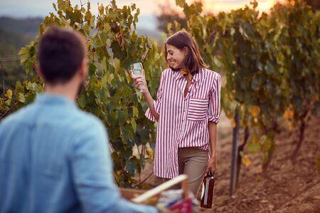 Happy farming woman with wine on autumn vineyard Stock Photo