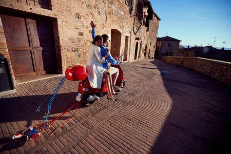 recién casado feliz hombre y mujer montando scooter.