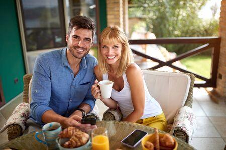 Cheerful pair having breakfast on terrace