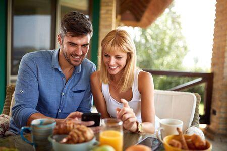 Happy couple having breakfast on terrace