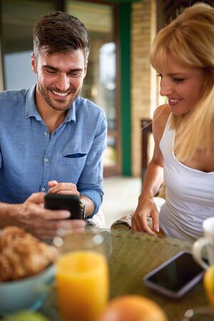 Male and female amusing with cell phone during breakfast Stok Fotoğraf