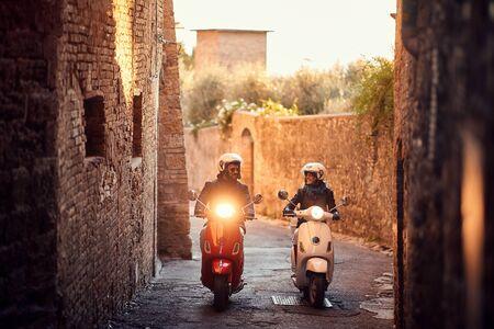Sonriente joven hombre y mujer montando moto en la ciudad. Ciclistas en la carretera.