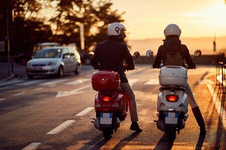Pareja joven montando moto en la carretera al atardecer. Foto de archivo
