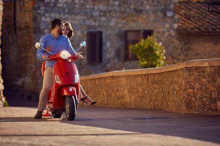 Recién casados feliz hombre y mujer montando moto en la ciudad.