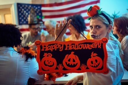 Spooky happy friends in costumes at Halloween Party. Stock Photo