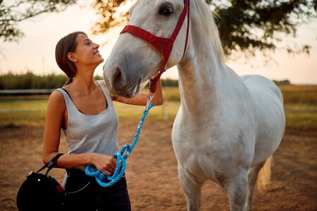 Young woman with horse. Pretty girl at horse ranch.