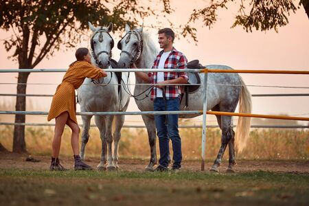 Young happy couple preparing their horses for a ride on farm