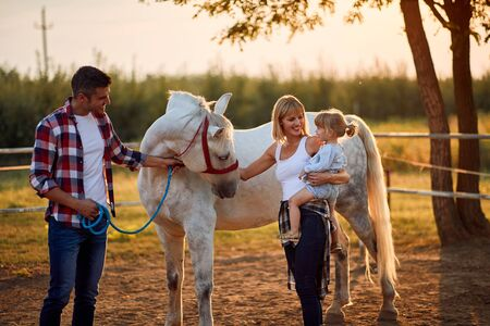 Happy family with girl petting horses in countryside