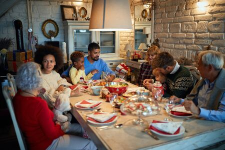 Happy Family and smiling friends dining at home celebrating christmas eve with traditional food