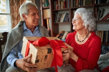 Smiling senior man and woman Exchanging Christmas Gifts
