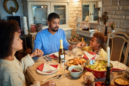 Family dining at home celebrating christmas eve with traditional food and decoration, praying