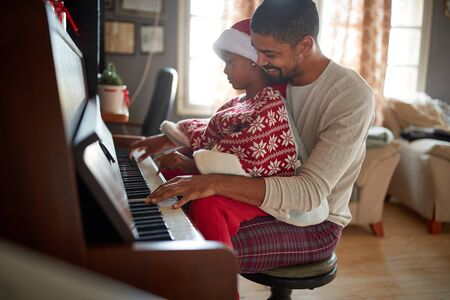 father with child girl on Christmas morning play music on piano.