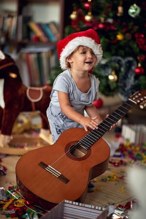 Cute boy in Santa hat is playing in front of a decorated Christmas tree with guitar 版權商用圖片