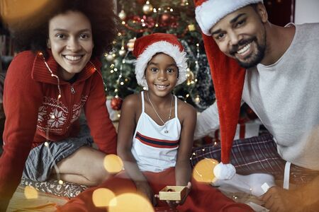 Smiling young family on Christmas morning celebrating holiday