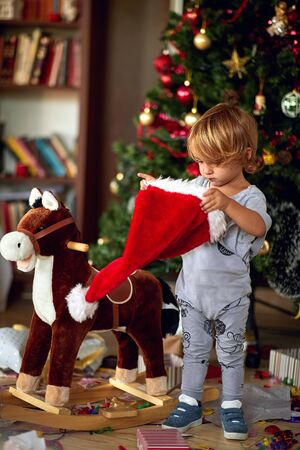 Cute boy is playing with Santa hat in front of a decorated Christmas tree 版權商用圖片