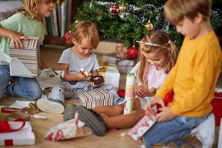 Children opening Xmas presents. Smilin kids gunder Christmas tree with gift boxes.