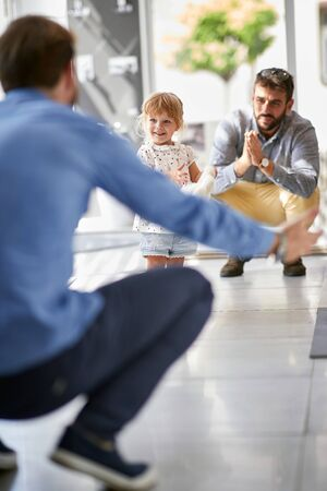 Happy fathers with smiling child girl in store