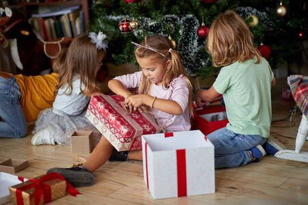 Kids opening Xmas presents. Cute Children under Christmas tree with gift boxes. 版權商用圖片