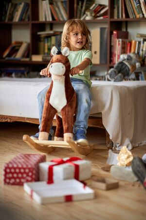 Small cute boy riding wooden rocking horse in front of christmas tree 版權商用圖片