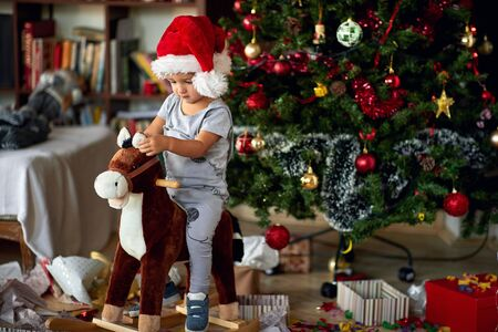 Small cute boy in Santa hat riding wooden rocking horse in front of christmas tree 版權商用圖片