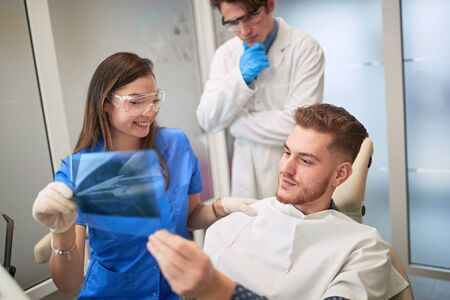 Smiling Doctor dentist showing young patient's teeth on X-ray Imagens