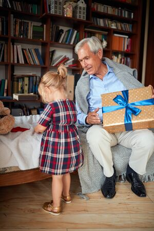 Happy grandfather  with presents spending Christmas together with his granddaughter