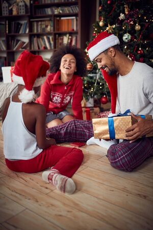 Happy young  Family exchanging gifts in front of decorated Christmas tree Stock Photo