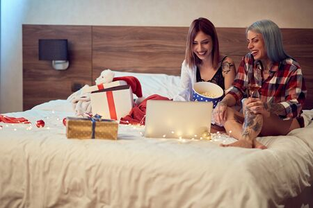 Christmas shopping at home.woman looking on laptop in bed. Stock Photo