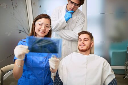 Dentist with female assistant looking patient's X-ray of teeth