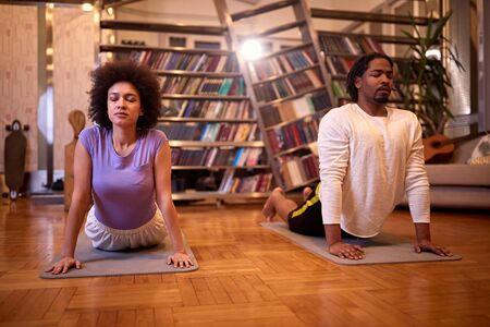 Woman and man practicing yoga indoor
