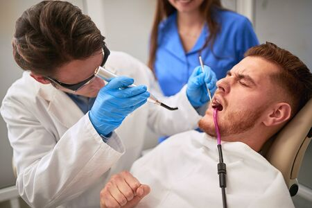 Male patient at dentist in dental chair having toothache Imagens