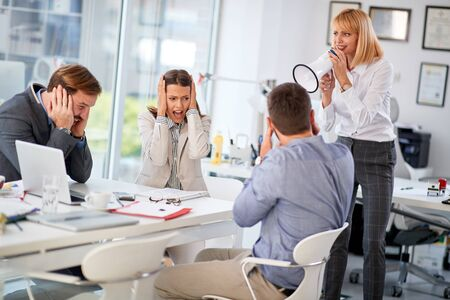 angry businesswoman with megaphone in office yelling