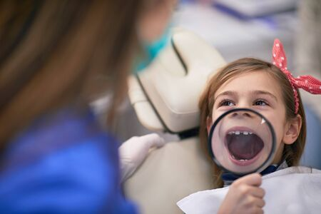 Little girl in dental office with opened magnified mouth