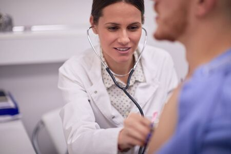 Doctor listening to the heartbeats of her patient with stethoscope