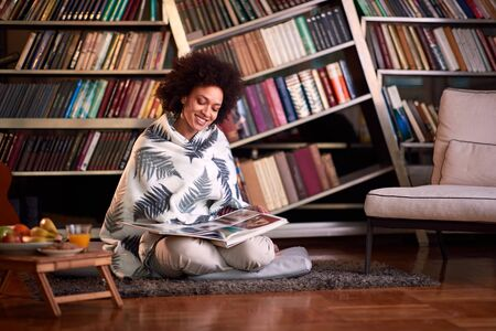 Female in home library sitting on the floor and looking in book