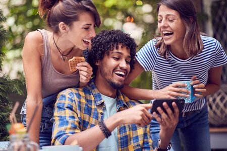 group of young smiling friends looking to phone and talking outdoor while having a coffee time.