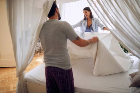 sexy young couple in underwear making the bed in the bright morning. Togetherness, happy, fun and valentine's day concept