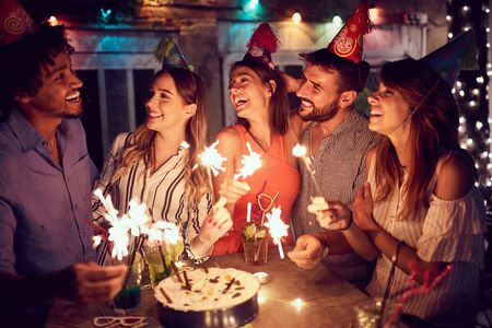Cheerful group of young friends having  birthday party in the club with cake and candles at night.  Party, fun, birthday concept. Zdjęcie Seryjne