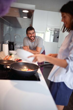 Happy man and woman  together prepare breakfast at home.