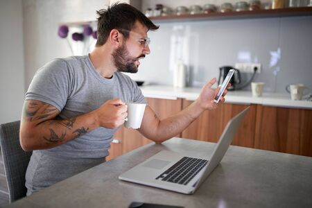 man in pajamas use his phone during breakfast at home.