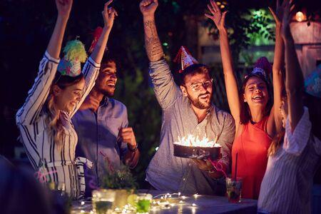 Allegro gruppo di giovani amici che hanno festa di compleanno nel club con torta e candele di notte. Festa, divertimento, concetto di compleanno.