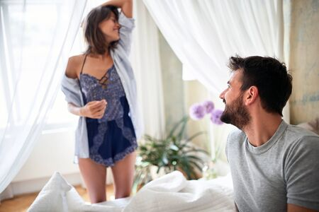 young sexy couple in underwear having a dance in bed in the bright morning on valentine's day. Intimacy, passion, erotic concept.