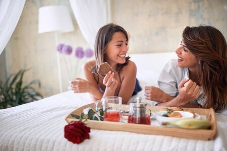 young sexy homosexual couple in bed having healthy breakfast on valentine's day. Love, Romance and morning concept.